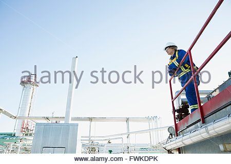 Female worker on platform overlooking gas plant - Stock Photo