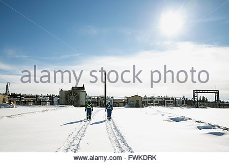 Workers walking in snow toward gas plant - Stock Photo