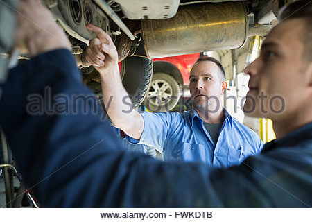 Mechanics working under car in auto repair shop - Stock Photo