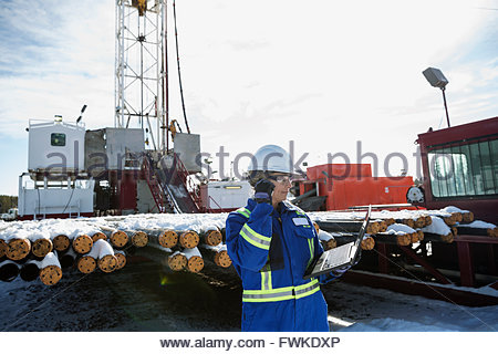 Female engineer with laptop working at gas plant - Stock Photo