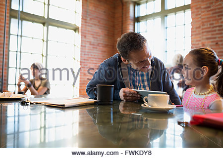 Father and daughter using digital tablet in coffee shop - Stock Photo