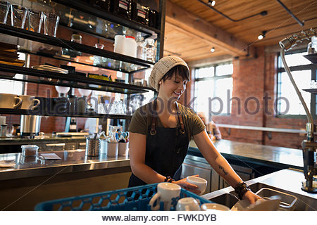 Worker doing dishes in coffee shop - Stock Photo