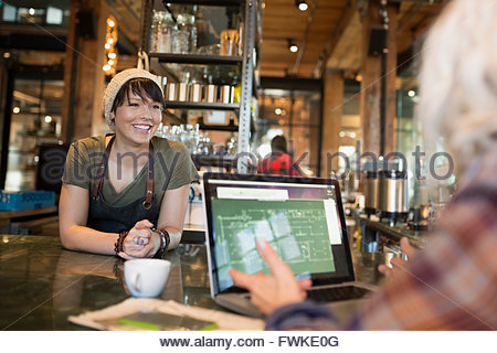 Barista talking to woman at laptop in coffee shop - Stock Photo