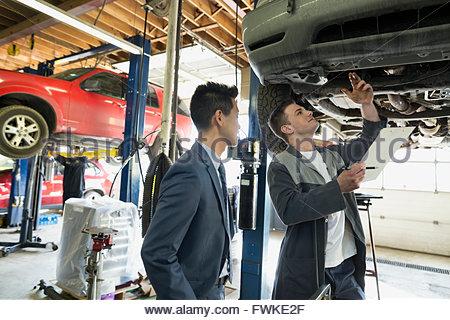 Mechanic and customer under car auto repair shop - Stock Photo
