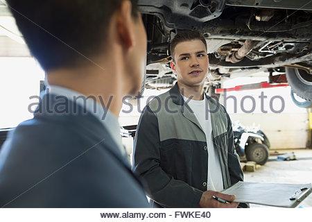 Mechanic talking to customer in auto repair shop - Stock Photo