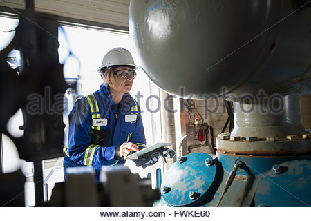 Female engineer digital tablet examining equipment gas plant - Stock Photo