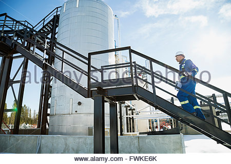 Male worker ascending platform stairs at gas plant - Stock Photo