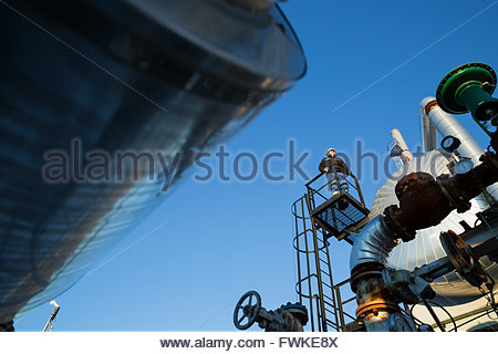 Male engineer standing on platform above gas plant - Stock Photo