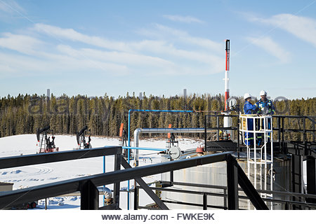 Workers on platform at gas plant - Stock Photo