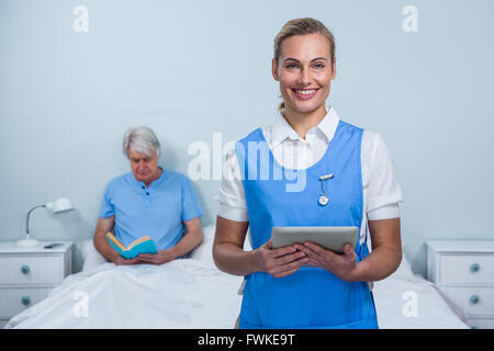 Smiling nurse holding digital tablet at hospital - Stock Photo