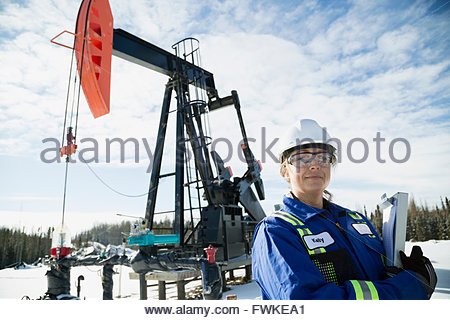Portrait confident female engineer drilling rig in snow - Stock Photo