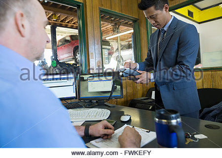 Customer using credit card reader auto shop office - Stock Photo