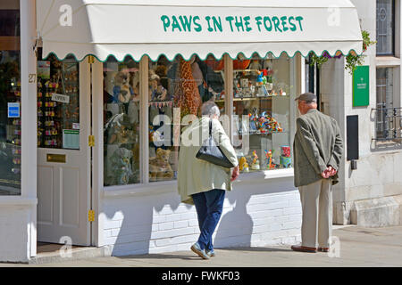 Couple browsing High Street window shopping outside Paws In The Forest  a toyshop specialising in bears in Lyndhurst - Stock Photo