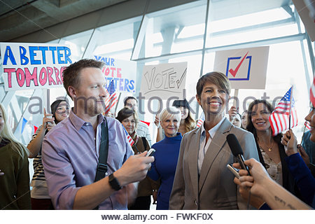 Female politician being interviewed among crowd at rally - Stock Photo
