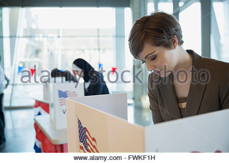 Young woman in voting booth at polling place - Stock Photo