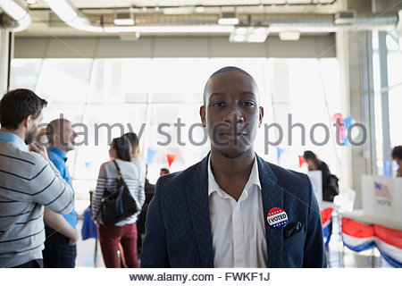 Portrait confident young man at voter polling place - Stock Photo