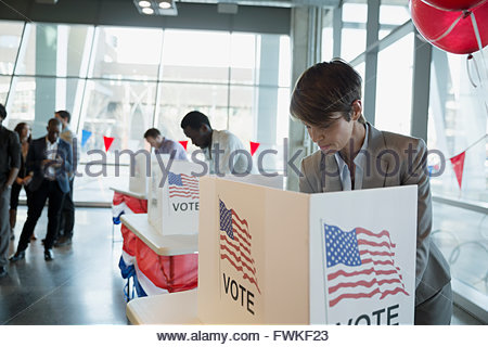 Woman in voting booth at polling place - Stock Photo