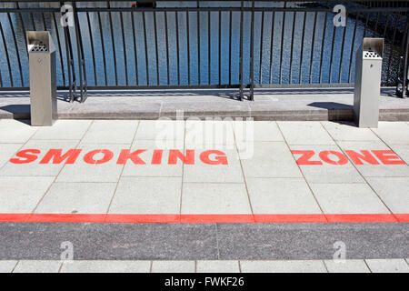 Pavement markings designated Smoking Zone in open space amongst office blocks at Canary Wharf London Docklands Isle - Stock Photo