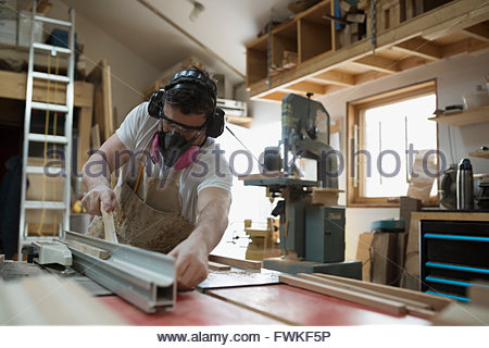 Carpenter wearing protective mask in workshop - Stock Photo