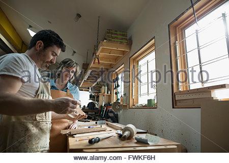 Carpenters examining wood piece in workshop - Stock Photo
