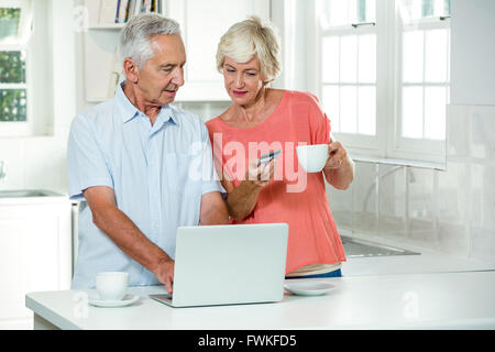 Senior couple with credit card while using laptop - Stock Photo