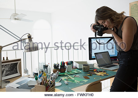 Craftswoman photographing pieces on desk in home office - Stock Photo