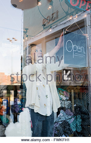 Smiling shop owner turning Open sign at window - Stock Photo