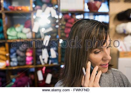 Yarn store owner talking on telephone - Stock Photo
