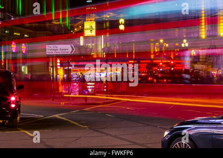 London Bus light trails night time Piccadilly circus black Cab taxi long exposure - Stock Photo