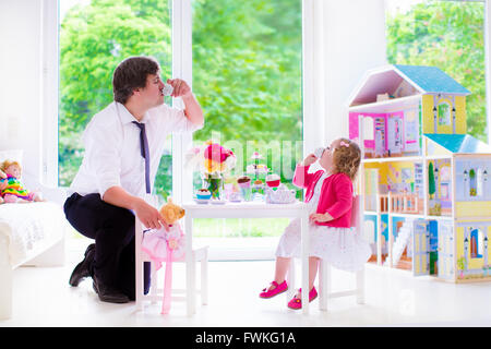 Happy family, young father and his little daughter, cute curly toddler girl wearing a dress, playing together with - Stock Photo