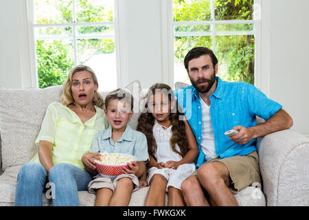 Portrait of surprised family laughing while watching tv - Stock Photo