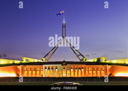 Building of Parliament on Capitol hill in Canberra - facade, entrance and columns illuminated with tall mast and - Stock Photo