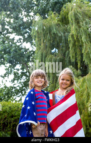 Portrait of siblings wrapped in American flag at back yard - Stock Photo