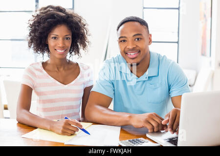 Young couple using laptop while checking bills - Stock Photo