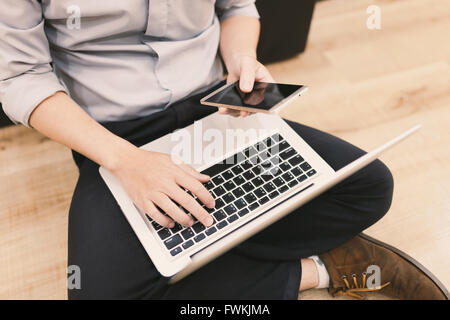 Top view man typing text message on his smart phone while sitting front open laptop computer, office man connecting - Stock Photo