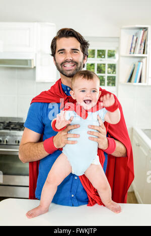 Happy father and son in superhero costume at home - Stock Photo