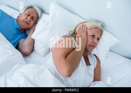 Senior woman blocking ears while man snoring - Stock Photo