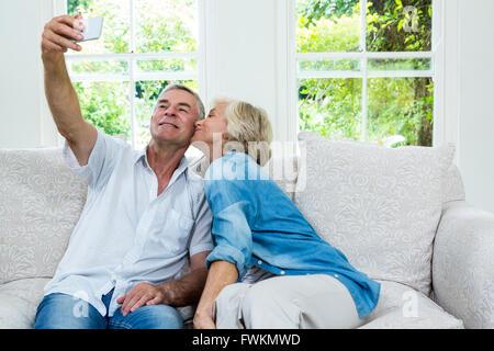 Senior woman kissing while man taking selfie in sitting room - Stock Photo