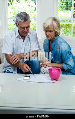 Senior couple calculating savings at home - Stock Photo
