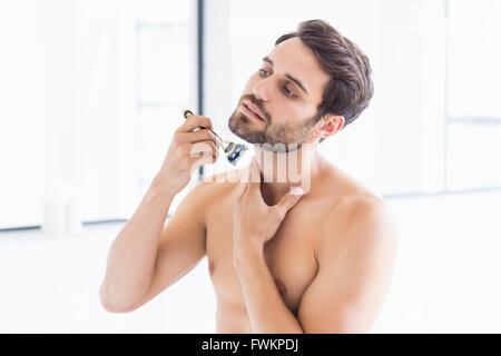 Man shaving in the bathroom - Stock Photo