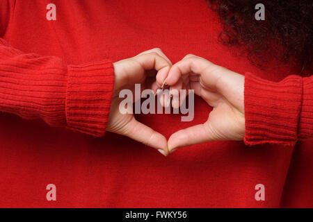 Midsection Of Woman Making Heart Shape Through Hands - Stock Photo