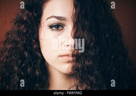 Close-Up Portrait Of Woman With Curly Hair - Stock Photo