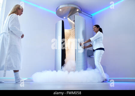 Full length portrait of nurse opening the door of cryosauna, with woman in bathrobe at the clinic. Female going - Stock Photo