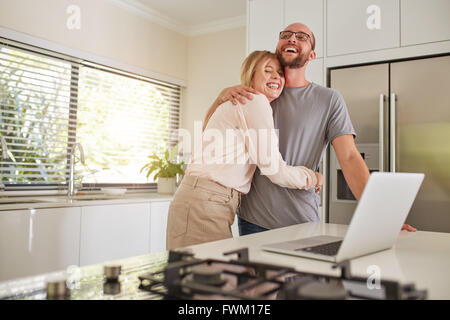 Portrait of happy woman embracing her husband in kitchen. Loving couple with laptop on  kitchen counter at home. - Stock Photo