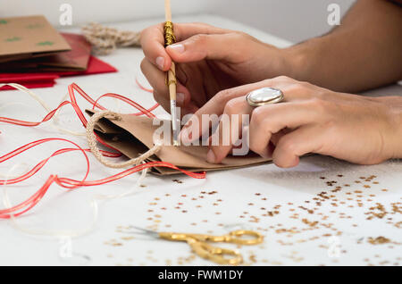 Cropped Image Of Hand Decorating Paper Bag On Table - Stock Photo