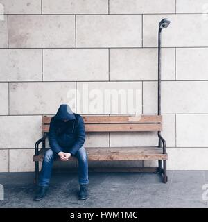 Man Sitting On Bench Against Wall - Stock Photo