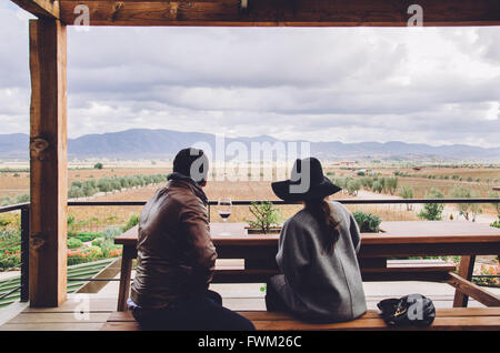 Rear View Of Friends Sitting On Bench In Gazebo Against Landscape - Stock Photo