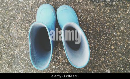 Directly Above Shot Of Rubber Boots On Street - Stock Photo