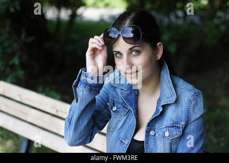 Portrait Of Beautiful Young Woman Wearing Sunglasses While Sitting On Bench - Stock Photo