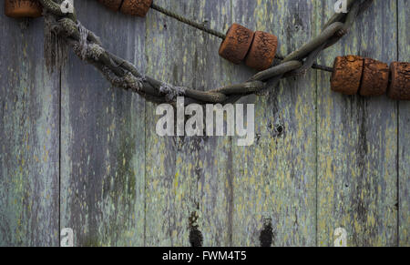 Old, grungy, antique, vintage fishing equipment on a wood background.  Includes rope and floats - Stock Photo